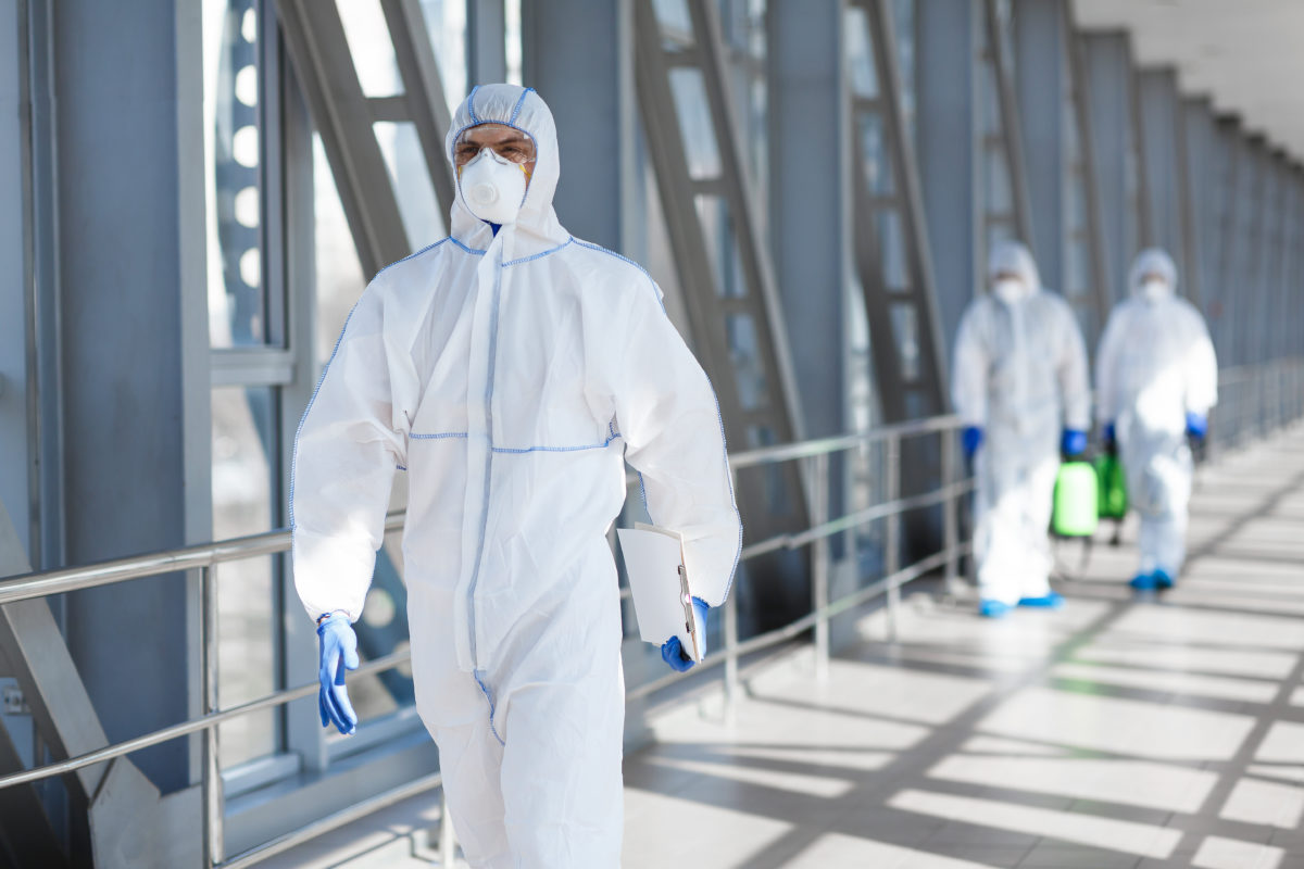 disinfecting company wearing PPE gear suits